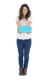 Cheerful casual brunette offering a present Royalty Free Stock Photo