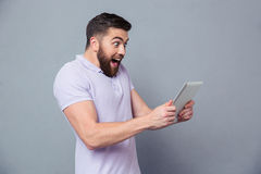 Cheerful casual man using tablet computer Stock Images