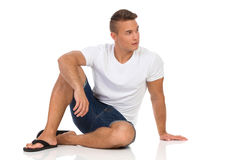 Cheerful Casual Man In White Shirt Sitting On Floor royalty free stock photos