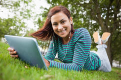 Cheerful casual student lying on grass using tablet Royalty Free Stock Photos