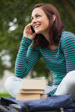 Cheerful casual student sitting on bench phoning Royalty Free Stock Photography