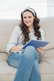 Cheerful casual woman on cosy couch using tablet pc Royalty Free Stock Photo