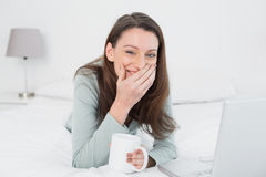 Cheerful casual woman with laptop and cup in bed. Portrait of a cheerful relaxed casual young woman with laptop and cup in bed at home Stock Images