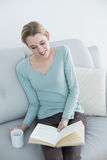 Cheerful casual woman reading a book holding a cup Royalty Free Stock Photo