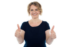 Cheerful casual woman showing double thumbs up Stock Photos