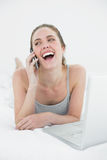 Cheerful casual woman using cellphone and laptop Stock Photo
