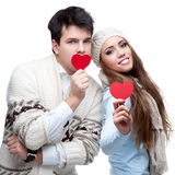 Cheerful casual young couple holding red hearts Royalty Free Stock Photos