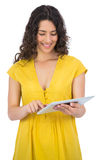 Cheerful casual young woman scrolling on her tablet computer Stock Photography