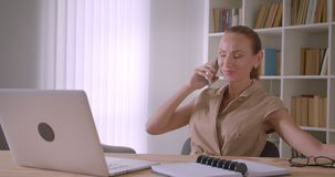 Cheerful caucasian businesswoman sitting in front of laptop and talks on cellphone being relaxed in office. Cheerful caucasian businesswoman sitting in front of stock video