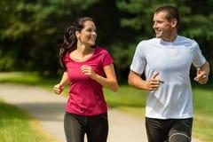 Cheerful Caucasian couple running outdoors Stock Photo