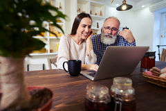 Cheerful Caucasian female works with senior man in a friendly wa Stock Photos