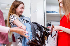 Cheerful Caucasian girl buying or choosing jeans with a shop assistant in a clothing store.  Stock Photos
