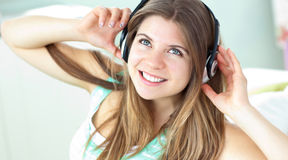 Cheerful caucasian girl listening to music sitting