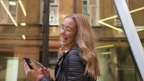 Cheerful caucasian girl in stylish glasses walking on the street in sunny day and texting on the smart phone. Outdoors. Cheerful caucasian girl in stylish stock video