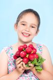 Cheerful caucasian little girl holding a radish Royalty Free Stock Photography
