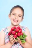 Cheerful caucasian little girl holding a radish Royalty Free Stock Photo