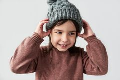 Cheerful Caucasian little girl in the winter warm gray hat, smiling and wearing sweater isolated on a white studio background royalty free stock image