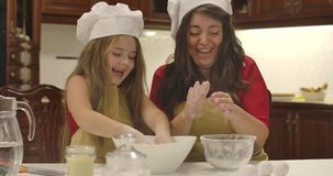 Cheerful Caucasian mother and daughter cooking together at the kitchen. Little girl clapping hands and flour flying stock video footage