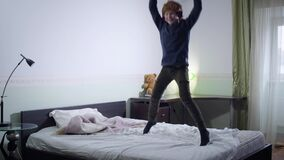Cheerful Caucasian redhead boy in headphones jumping on bed and gesturing emotionally. Happy little kid falling down on