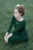Cheerful caucasian woman with green eyes and green dress looking Royalty Free Stock Photo