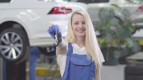 Cheerful Caucasian woman standing at the background of car and showing car keys to camera. Blond female auto mechanic