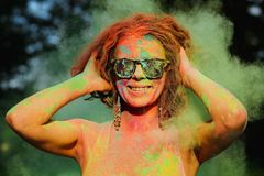 Cheerful caucasian model wearing sunglasses, posing in a cloud o. Cheerful caucasian woman wearing sunglasses, posing in a cloud of green Holi paint royalty free stock photography