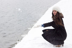 Cheerful Caucasian Young Woman in Snowy Weather throws a snowbal Stock Photo