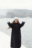 Cheerful Caucasian Young Woman in Snowy Weather throws a snowbal Stock Images