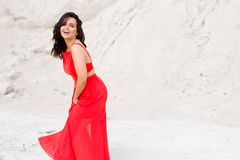 Cheerful charismatic girl in red dress with bare shoulders, poses outside in wilderness royalty free stock photo
