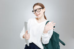 Cheerful charming girl student holding laptop and waving with hand Royalty Free Stock Images