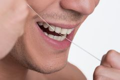 Cheerful charming guy is taking care of hygiene. Dental health. Close-up of male mouth. Joyful young man is flossing his teeth and smiling. Isolated background Royalty Free Stock Photos