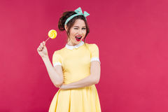 Cheerful charming pinup girl with yellow lollipop standing and w. Inking over pink background royalty free stock photography