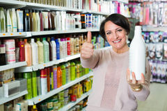 Cheerful charming woman choosing hair care products. In shop and smiling stock photo