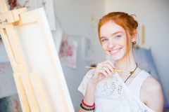 Cheerful charming young female artist painting  with paintbrush on canvas Royalty Free Stock Photo