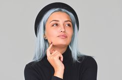 Cheerful and charming young teenager woman with blue hair wearing black apparel and hat, smiling, looking up. Cute positive female. Posing on light grey stock images