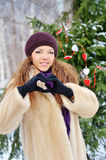 Cheerful charming young woman in a fur coat makes heart fingers Royalty Free Stock Photography