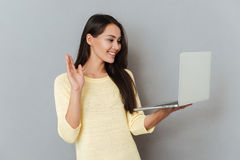 Cheerful charming young woman holding laptop and having video conference. Over grey background Stock Images
