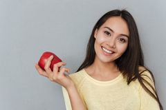 Cheerful Charming Young Woman Holding Red Apple Royalty Free Stock Image