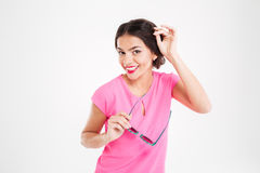 Cheerful charming young woman posing and holding sunglasses Royalty Free Stock Photos