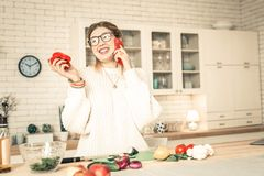 Cheerful chatty lady in white oversize sweater pleasantly talking. Break in cooking. Cheerful chatty lady in white oversize sweater pleasantly talking while stock photos