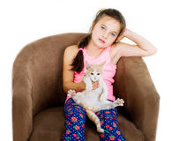 Cheerful cheerful child girl plays with a little kitten on a light background Stock Photo