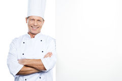 Cheerful chef. Confident mature chef in white uniform leaning at the copy space and smiling while standing against white background stock images