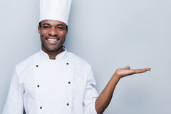 Cheerful chef. Confident young African chef in white uniform holding copy space and smiling while standing against grey background Royalty Free Stock Photos