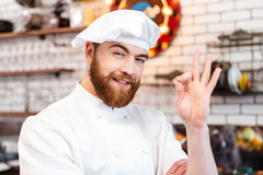 Cheerful chef cook showing ok sign on the kitchen Stock Image