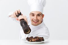 Cheerful chef cook wearing uniform peppers. Cooked beef steak on a plate isolated over white background stock image