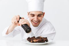 Cheerful chef cook wearing uniform peppers. Cooked beef steak on a plate isolated over white background stock photos