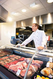 Cheerful chef on the counter of frozen meat Royalty Free Stock Photo