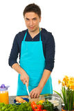 Cheerful chef cutting green onion. Cheerful chef man cutting green onion in kitchen Royalty Free Stock Photography