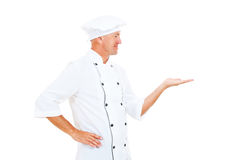 Cheerful chef holding something on his palm Royalty Free Stock Images