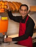 Cheerful chef making fresh orange juice Stock Images